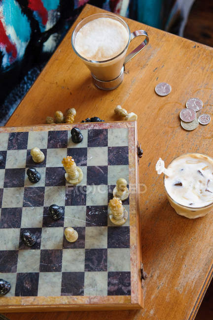 Chess board with drinks and coins on table — Stock Photo