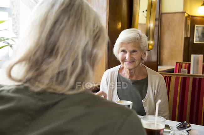 Мать и дочь сидят вместе в кафе — стоковое фото