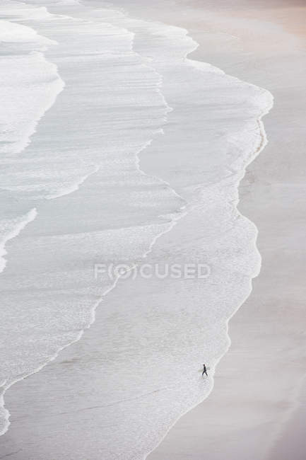 Aerial view of beach with waves and person with surfing board — Stock Photo