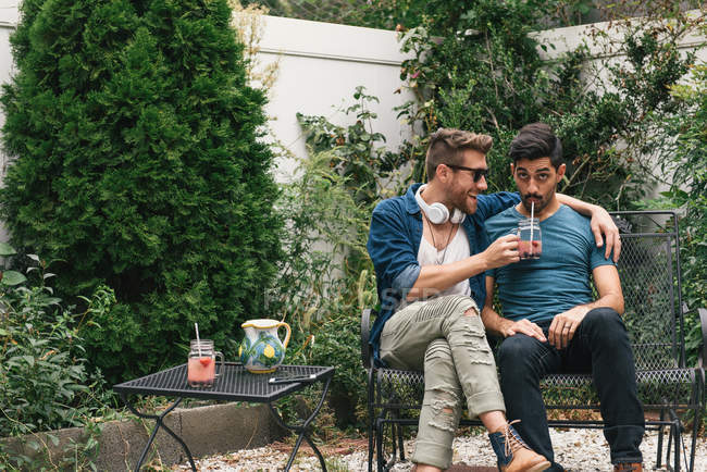 Young male couple sitting in garden drinking cocktails — Stock Photo