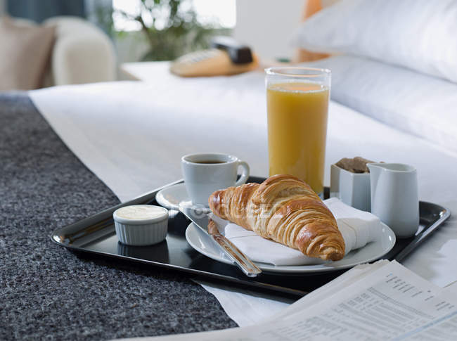 Breakfast tray with coffee, croissant and glass of juice on bed — Stock Photo