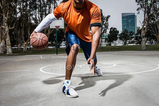 Молодой человек играет в баскетбол на площадке, крупным планом — стоковое фото