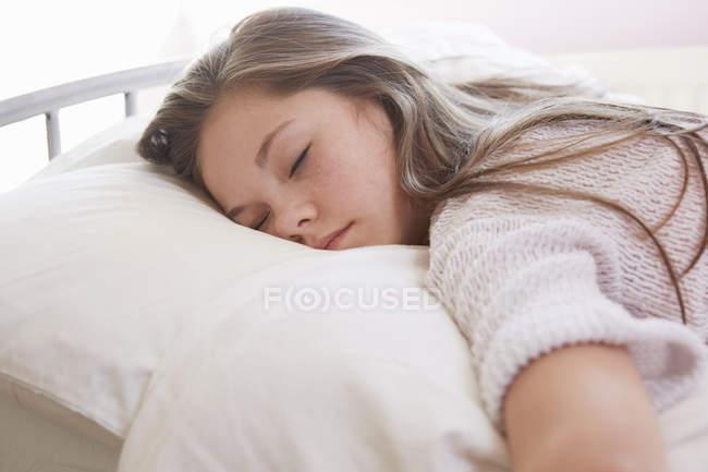 Girl lying on bed asleep — Stock Photo