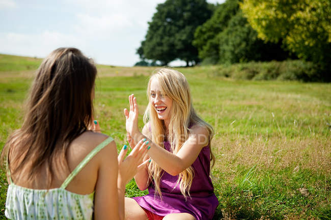 Young women playing patacake in a field — Stock Photo