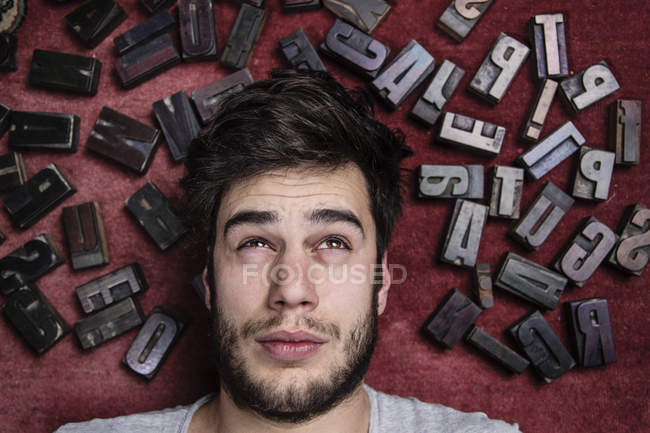 Young man with letterpress letters surrounding his head — Stock Photo