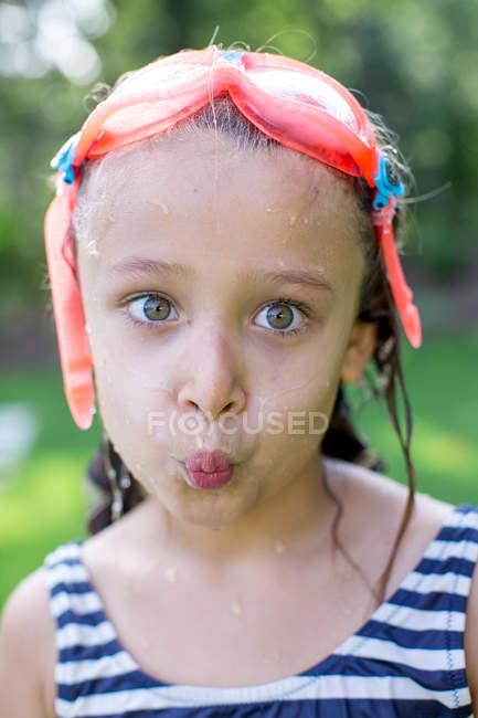 Portrait of girl in swimming goggles puckering lips in garden — Stock Photo