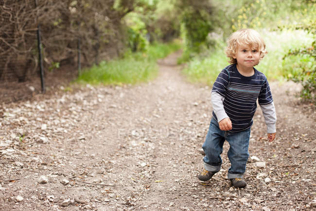 Boy walking on dirt track — Stock Photo