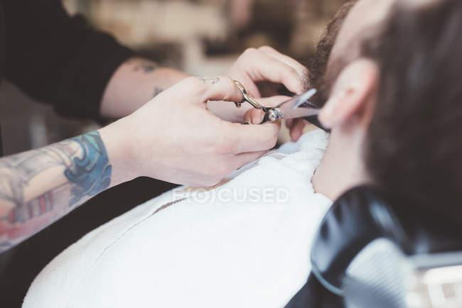 Крупный барбер обрезки клиента борода в парикмахерской — стоковое фото