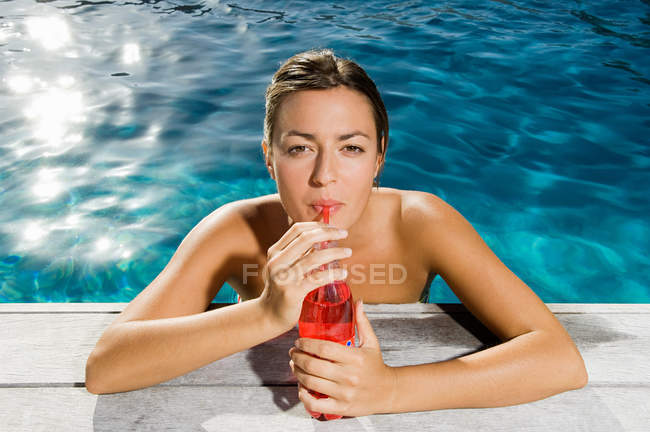 Young woman drinking soft drink at poolside — Stock Photo