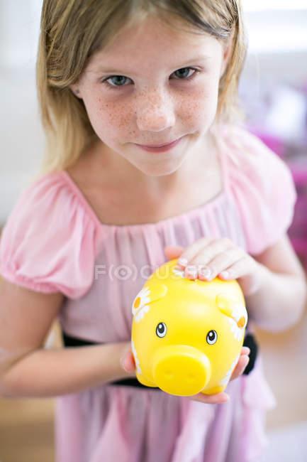 Porträt eines Mädchens mit Sparschwein — Stockfoto