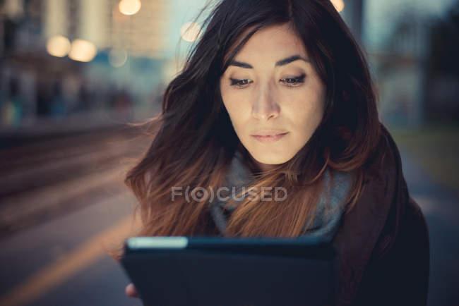 Mid adult woman using digital tablet touchscreen on railway platform at dusk — Stock Photo