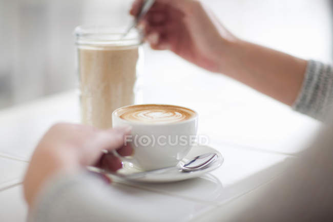 Female hands with coffee cup and glass — Stock Photo