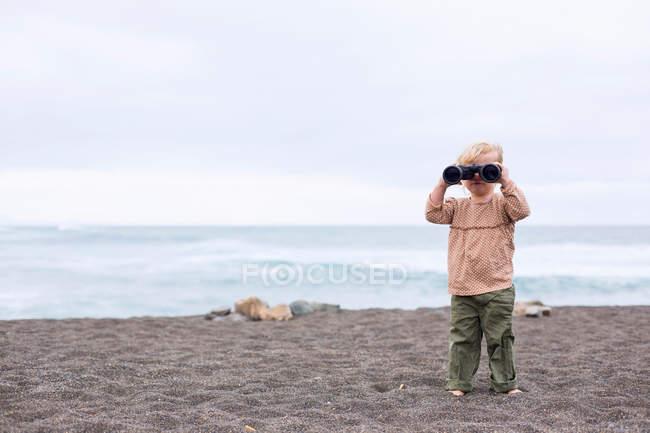 Niña usando prismáticos en la playa - foto de stock