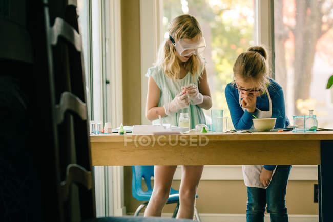 Две девушки проводят научный эксперимент, читая инструкции — стоковое фото