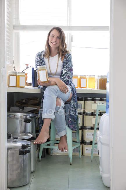 Mujer sosteniendo tarro de producto casero - foto de stock