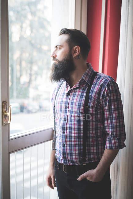 Giovane uomo in bretelle guardando fuori porta barbuto — Foto stock