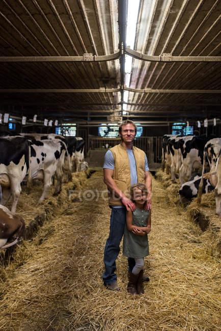 Porträt von Bauer und Tochter im Kuhstall — Stockfoto