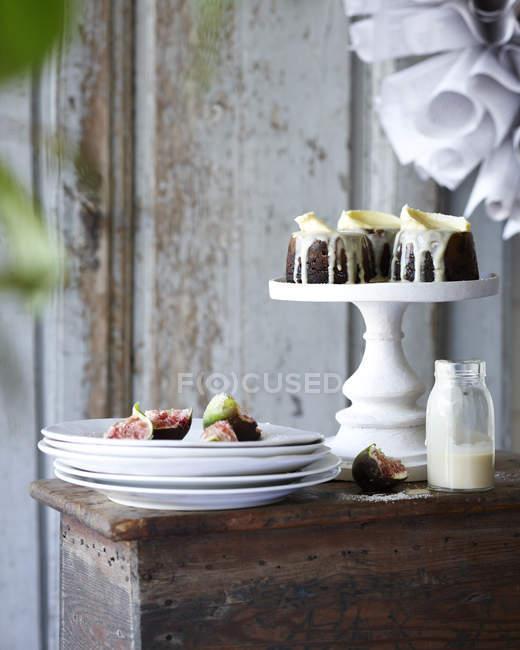 Puddings de Noël mini avec des figues sur la pile de plaques sur la table de patio — Photo de stock