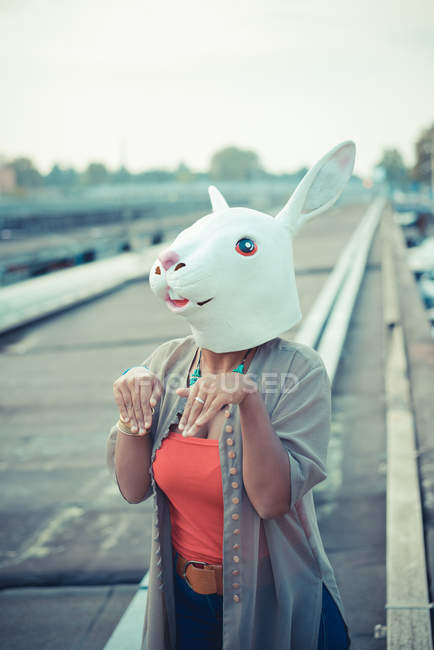 Young woman in rabbit costume mask in city — Stock Photo