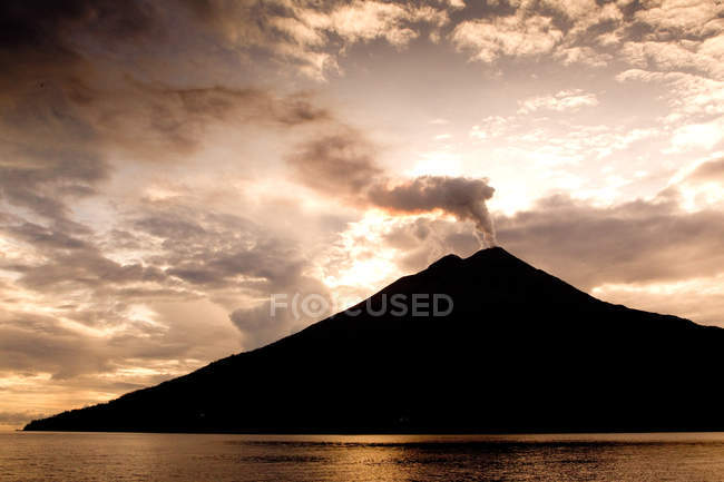Erupting volcano silhouette above water with cloudy sky — Stock Photo