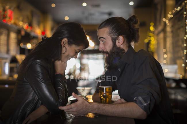 Giovane coppia che parla a tavola con cocktail e birra nella casa pubblica — Foto stock