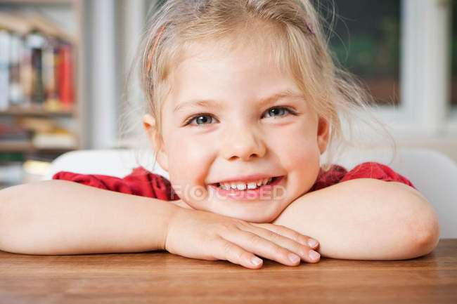 Smiling girl resting on elbows — Stock Photo