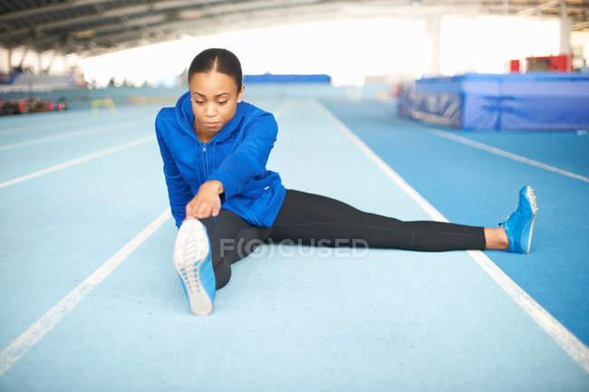 Jeune athlète féminine assis sur sol toucher les orteils — Photo de stock