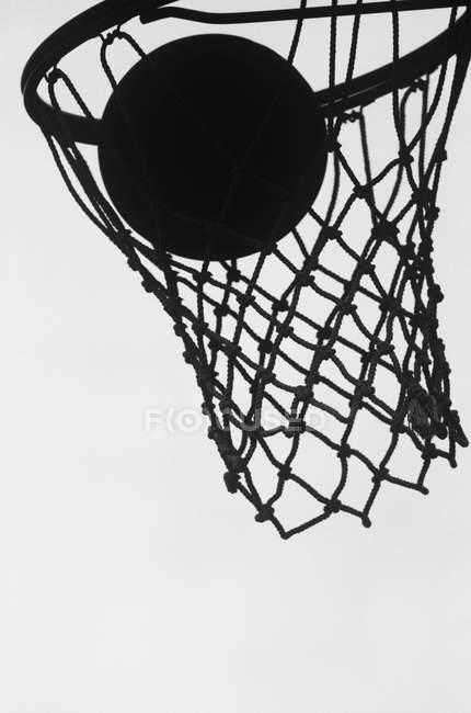 Силуэт баскетбольного кольца и мяча против неба, крупный план — стоковое фото