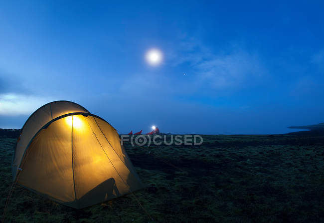 Glowing tent at campsite, man in background — Foto stock