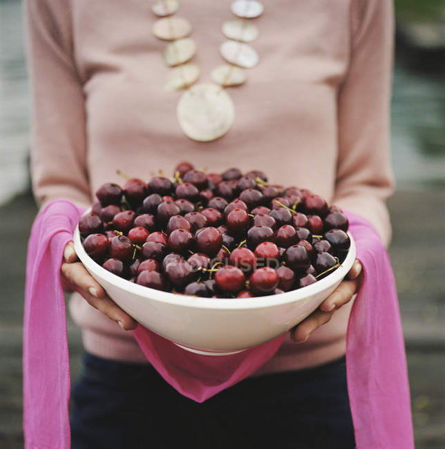 Woman holding bowl of red cherries — Stock Photo