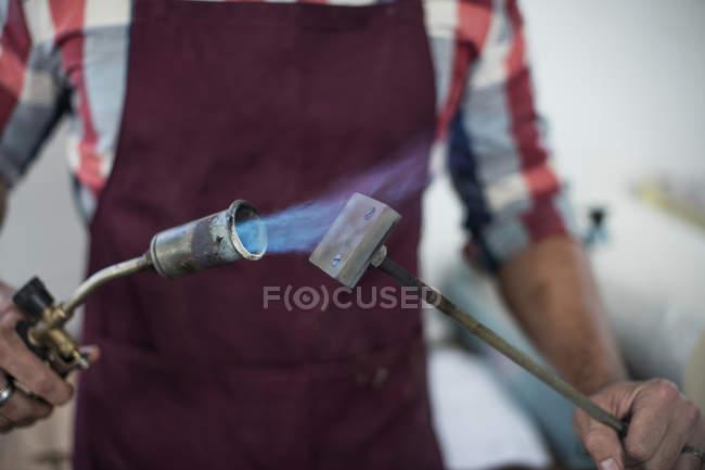 Section médiane de l'homme chauffant le fer de marque avec torche soufflante dans l'usine — Photo de stock
