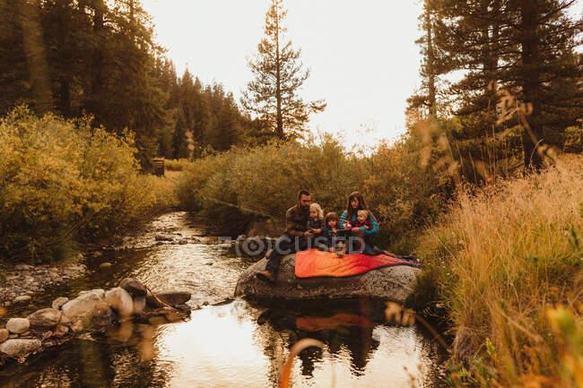 Família sentada na rocha ao lado do riacho, pesca, Rei Mineral, Parque Nacional Sequoia, Califórnia, EUA — Fotografia de Stock
