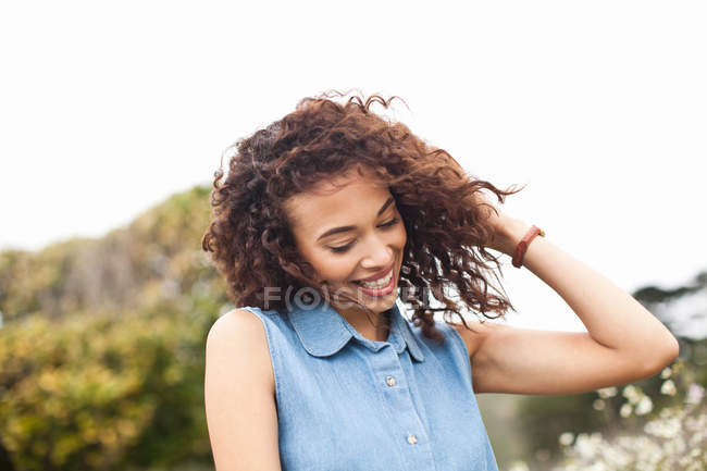 Young woman with hand in hair, smiling — Stock Photo