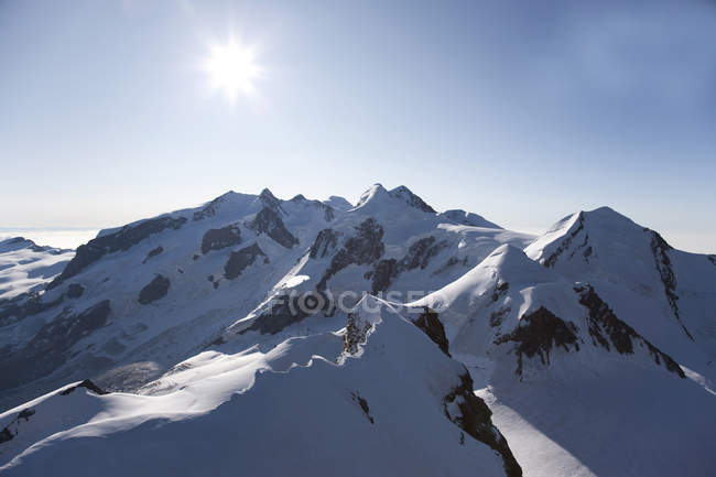 Snowcapped rocky mountains with shining sun — Stock Photo