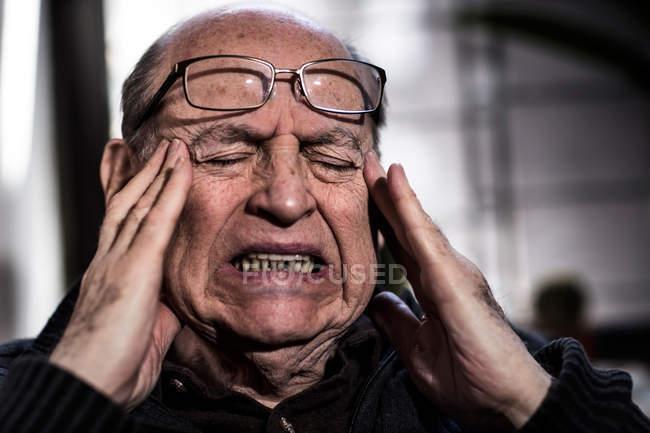 Старший мужчина с закрытыми глазами, в очках, глядя подчеркнул — стоковое фото