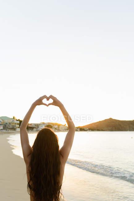 Rear view of woman making heart shape around sunlight — Stock Photo