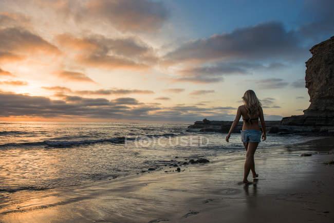 Jovem mulher andando na praia ao pôr do sol, vista traseira — Fotografia de Stock