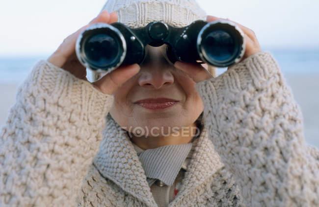 Senior woman using binoculars — Stock Photo