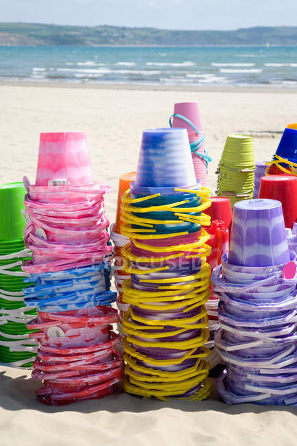 Stacks of buckets on sandy beach in sunlight — Stock Photo