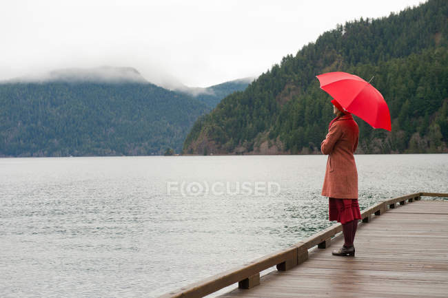 Woman With Umbrella On Wooden Pier Side View One Person Stock