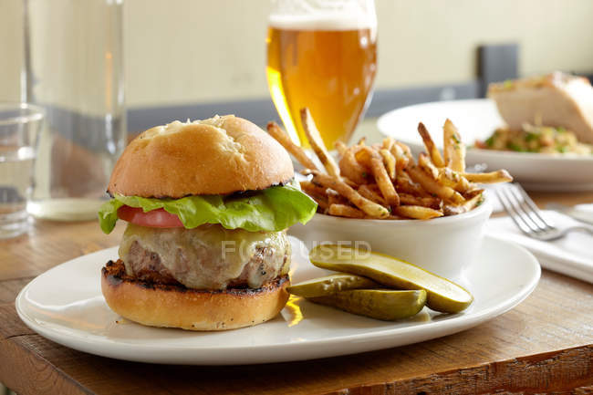 Front view of burger and fries on restaurant table with beer — Stock Photo