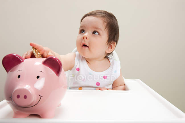 Baby boy sitting in highchair with piggy bank and coins — Stockfoto