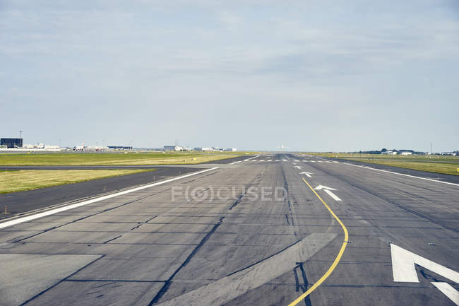 Diminishing perspective of airport runway under blue sky — Stock Photo