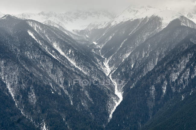 Valley and snowcapped mountains covered in fog — Stock Photo