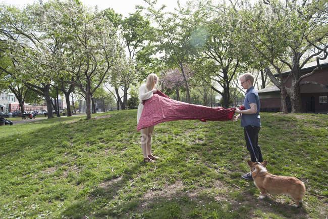 Young couple shaking picnic blanket in park — Stock Photo