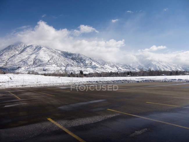 Empty parking lot with snow covered Wasatch Mountains — Stock Photo