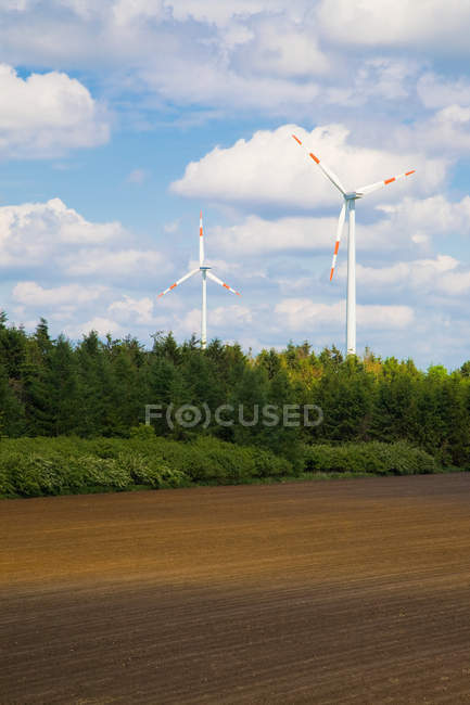 Wind turbines and field under blue cloudy sky — Stock Photo