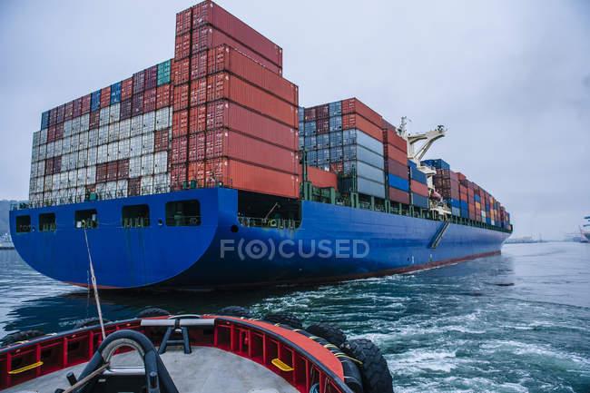 Tugboat manoeuvring container ship on river, Tacoma, Washington, USA — Stock Photo