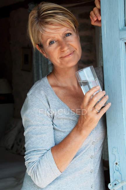 Портрет женщины в дверях с питьевой водой — стоковое фото