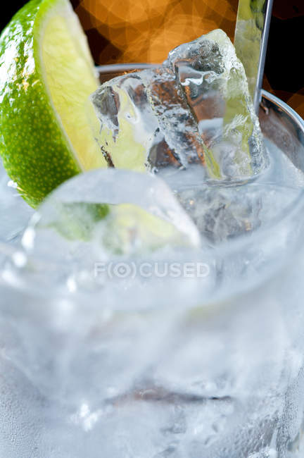Beverage with ice and lime slice — Stock Photo
